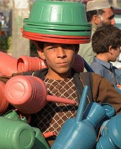 ENDS MEET: A boy sells plastic wares in Herat. Many Afghans struggle to make a living in an economy that despite making progress remains extremely poor, landlocked and highly dependent on foreign aid. (AFP)