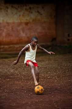"A boy in Mbouda, Cameroon, Africa plays soccer in bare feet. Here he works to get control of the ""football"" before the opponents close in on him."