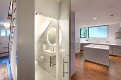 aménagement sous escalier avec WC, revêtement de sol en parquet massif, cuisine moderne avec îlot et plafond design