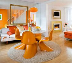 Now this is what I call a sexy room! The swooping lines of tangerine-orange Panton chairs, a glowing orange pendant, cheery orange walls, and saffron-orange silk cushions on the sofa imbue this room with energy, excitement and a fun and happy vibe. I love the textural contrasts, too, of the sleek & smooth Panton chairs against the oval shag rug.