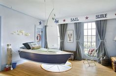 Nautical bedroom with suspended sailboat bed