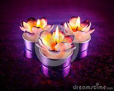 Close up of purple and orange flower shaped candles burning on purple reflective surface.