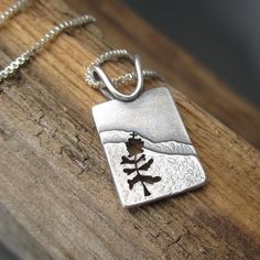 Handcrafted sterling silver pendant featuring an intricately hand-sawn pine tree, inspired by the many hemlock forests in the Upper Peninsula of Michigan. Product features: - Eco-friendly recycled ste