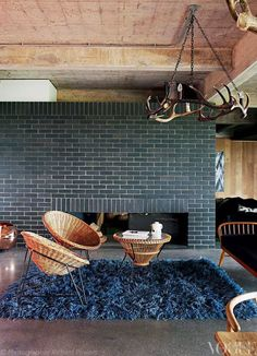 The living room of this disused reservoir in Kent was transformed into a contemporary family home. From Concrete Ambition, a story on page 134 of Vogue Living March Photograph by Richard ideas design and decoration Vogue Living, Glazed Brick, Black Fireplace, Fireplace Facade, Fireclay Tile, Black Brick, Brick Colors, Fireplace Remodel, Fireplace Redo