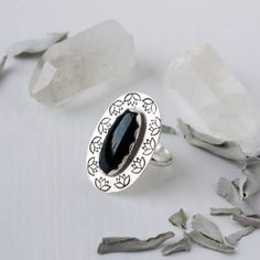 At ease in muddy waters ring.  One of a kind statement ring by Zenned Out Jewelry. Adorn yourself with a handmade black onyx ring that tells a story and has meaning.  Black onyx is said to help defend negative energy. The mud, gunk, and hard parts in life are sometimes what we need to blossom like the lotus. If you're in some mud let this black onyx surrounded by lotus flowers remind you that you're protected and that this phase will not last forever.