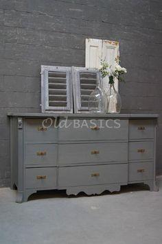 WWW.OLD-BASICS.NL - WEBSHOP Dressoir 10113 - Karaktervol oud dressoir in een koele grijze kleur. Deze stoere kast heeft negen lades die op slot kunnen. De voet van de kast is sierlijk afgewerkt, op beide zijlatten zit een leeuwenkop.