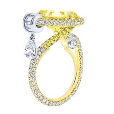 SOLEIL New Age Collection Featuring a 9.90ct. Fancy Yellow Round Brilliant Cut Diamond VVS2. GIA Certified # 13688921  With a 0.43 Ct. Pear cut diamond drop F color VS1 in clarity. The ring is also set with 0.48cts of Emerald Baguette Diamonds with F color and VS clarity and 0.30ct Fancy Yellow diamonds pave' set with VS clarity.The ring is also has 2.50cts of white brilliant round diamonds that are micro pave' set with F color and VS1 clarity.  1stdibs