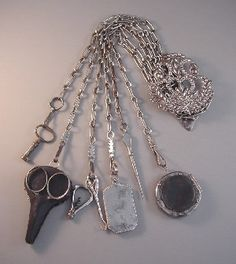 """1850 cut steel sewing chatelaine with 7 implements, 16-1/2"""" total length. The implements include a key, scissors with case, tiny corkscrew, aide memoire, sewing awl and round pin holder."""