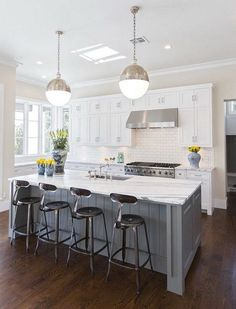 Classic white kitchen with white cabinets, darker floors,gray island and the modern pendants. More via http://forcreativejuice.com/elegant-white-kitchen-interior-designs/