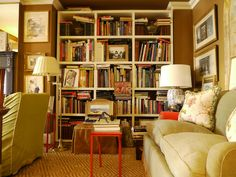1.8.10: Gerald Bland | New York Social Diary - The living room bookcases are literally stuffed with books on art and architecture.  Love this color scheme: brown & sage green with accents of cream & red.