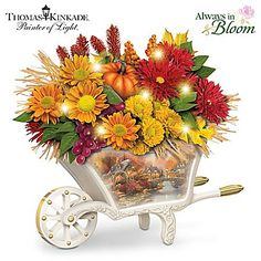 A limited-edition FIRST! Illuminated Always in Bloom® autumn floral arrangement in a handcrafted wheelbarrow vase boasting Thomas Kinkade artwork. Kitchen Centerpiece, Table Centerpieces, Art Thomas, Thomas Kinkade, Fall Is Here, Flower Art, Floral Arrangements, Floral Wreath, Christmas Decorations