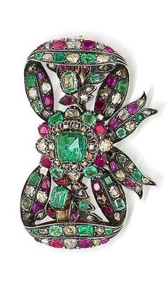 A 19th century emerald, ruby and diamond bow brooch, Hungarian The tied ribbon bow set throughout with vari-cut diamonds, rubies and emeralds, some in foiled closed-back settings, with a central inverted square-cut emerald, mounted in silver and gold, detachable brooch fitting, length 5.2cm