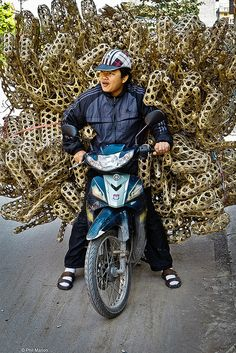 Motorcyclist loaded with bamboo cages - Vietnam http://hoianfoodtour.com/