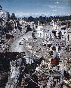 demons:  Two young French boys watching US jeeps and armor move through their destroyed village, c. 10 June 1944