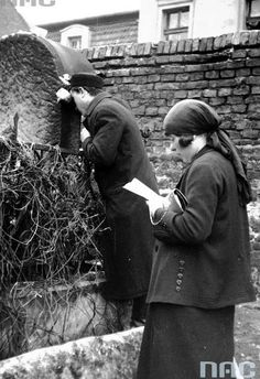 Feast of the of Rabbi Remuh on the Remuh Cemetery in Krakow (May 1931). Woman and man during modliwy on one of the matzevas.