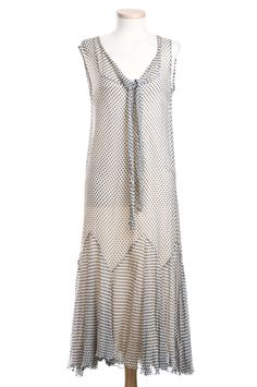 The Charleston Museum. Black and white dotted silk chiffon dress, 1920s. The sleeveless dress has a V neckline in front with a tapering collar extension ending in a long narrow tie. The little unlined jacket is open down the front and has long sleeves that flare out below the elbow, echoing the bias-cut, flared skirt which extends from a low, zig-zag seam.    This swingy flapper-era outfit was worn by Ruth Holmes Gadsden (1895-1980), who was well-known in Summerville, SC society circles.