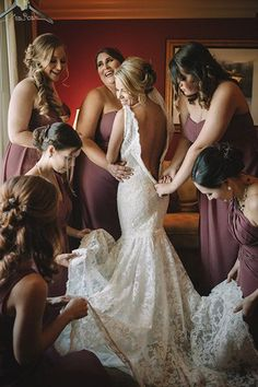 "50 photos to take of your wedding dress - Fawned Over by the Bridesmaids - ""I love photos of the mom, sisters, or bridesmaids helping the bride into her gown. It's such a sentimental moment!"" Schonevld says. A messy room can ruin the shot, so she recommends having your loved ones clear away any random items - bags, clothes, curling irons, etc. - from the background first."