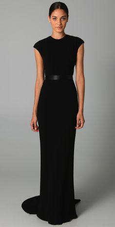 the combo of black t-shirt with sexy, fitted and floor length skirt all wrapped up in a jersey dress.  Throw on a bodacious brooch and rock it.