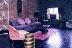 Rafael de Cardenas. A pink, red and gold geometric oriental rug is dramatized on a glossy black-purple wood floor in this romantic living room in a 10th Street apartment by Rafael de Cárdenas. A curved purple Art deco sofa and pink velvet chair look beautiful against a brick wall. A dark colored ornate wall paper covers the far wall. Image courtesy Rafael de Cárdenas.