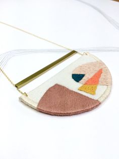 This stitched pendant was inspired by block printed and screen printed designs of the 1950s and 1960s.  The pendant is made from cream linen and is fully interfaced to provide support. I have stitched geometric shapes with the fabric on a hoop and then bound the edges using embroidery threads in Rose pink, Coral, Indigo, Mustard and Blush. This is suspended under a brass tube and hung from a chain of gold vermeil (sterling silver plated with 18ct gold). I have enamelled the brass tube to…