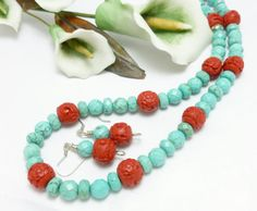 Eye-catching and bold turquoise colors with vibrant red beaded necklace. Made with turquoise colored magnesite faceted round and rondelle beads accented with 10mm red faux cinnabar beads  #CCMTT
