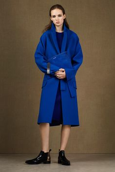 McQ Alexander McQueen - Pre-Fall 2015: she clutches the hairy clutch against the identically-coloured coat and you, in spite of not ever thinking of buying a coat of this shade of blue, suddenly want it
