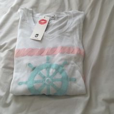 NWT WILDFOX V-Neck Knit Sweater ⚠️NEVER WORN⚠️ Super soft and comfortable knit v neck sweater with an image of a baby blue wheel of a boat on the front with lines of pink rope above and below it. Its super lightweight and great for layering. Price is negotiable, and the sweater is in perfect condition. Wildfox Sweaters V-Necks