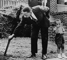 Dr. Martin Luther King pulling burned cross from his yard as his son stands aside.