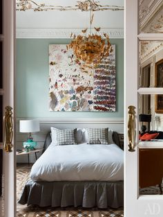 Beautiful sage green bedroom with abstract art & glorious gilded chandelier