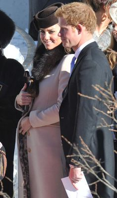 Royal petting ... Kate Middleton pats her baby bump next to Prince Harry