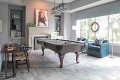 Contemporary game room features a linear filament pendant illuminating a pool table with fringed pockets facing a pair of turquoise leather armchairs with silver nailhead trim illuminated by matching white faux bois floor lamps.