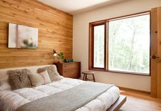 A wood wall and basic furniture for this bedroom of a house outside NY / Una parete di legno e arredi basic per questa camera in una casa fuori NY