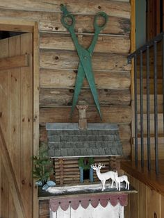 Oversize shears that once advertised a tailor hang over a toy log cabin that was found at a New Hampshire flea market.