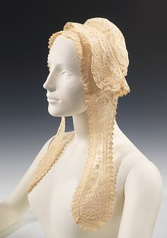 """Cap: ca. 1870, probably Irish, Carrickmackross lace.    """"A cap and lappets all in one is a somewhat unusual form, indicating a transitional period during the decline of lappets as fashionable headwear. The Carrickmackross lace used for this fine example has a rich textured appearance exhibiting fine workmanship."""""""
