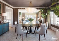 Jeffers hung a massive and ethereal cloud-like chandelier in the dining room above an understated diamond-patterned rug. Chairs by Thomas Pheasant Collection for Baker surround a Randolph & Hein table from Sloan Miyasato. Landscape designer Randy McDannell of RS McDannell selected the fig trees.