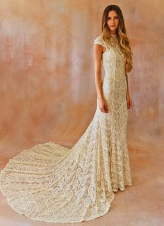 alice-ivory-lace-cap-sleeve-gown-in-simple-wedding-dresses by Dreamers & Lovers | The breathtaking Alice Dress is the picture of Boho-chic elegance. It features a semi-cathedral length train and cut-out back detail to add a sultry touch of drama. Delicately embroidered lace and scalloping throughout give the dress a vintage, feminine feel and the consistency of the fabric adds to the dramatic appeal of the gorgeous back detailing.