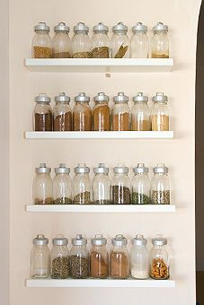 Spice rack: Jars set on shelves that are mounted to the wall.