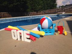 Baby boy first birthday photo shoot set up by the pool. Beach ball themed!