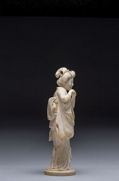 JAPANESE CARVED IVORY BEAUTY, MEIJI PERIOD (1868-1912) The standing beauty gracefully clasping her hands excited with her catch; signed.  Dimensions: Height 10 3/4 in. (27.3 cm.)