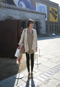 Neutrals in layers. Thick knit cardigan, long tunic, black leggings, suede flats, and a light scarf on her bag.