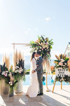 Poolside boho wedding ceremony with pampas grass, proteas, peonies and spray painted foliage | Andrew Clifforth Photography
