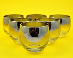 This is a beautiful set of vintage Roly Poly glasses from the 1950's. This style of rim where the silver gradually fades is called silver ombre and these particular glasses were made by Queens Lusterware who were known for their high quality silver flash fade glassware. These glasses sometimes get mislabeled as Dorothy Thorpe glassware, however Dorothy Thorpe actually made solid silver rim glassware with no ombre effect. However they still have the same Hollywood Regency feel to them, which…