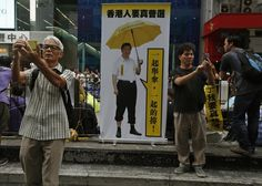 """HONGKONG-CHINA/ Local visitors take selfies in front of a manipulated photo of Chinese President Xi Jinping holding an umbrella, a symbol of the Occupy civil disobedience movement, at a road blocked by pro-democracy protesters at Mongkok shopping district October 27, 2014. Hong Kong has been roiled by a tenacious, student-led people's movement demanding full democracy in the former British colony that returned to Chinese rule in 1997. Chinese characters on the banner read, """"Hong Kong people…"""