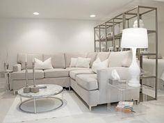 This contemporary white living room with a light gray sectional features metallic accents to make a clean, bold statement. A white lamp sits on a clear acrylic end table while the oversized candle holders atop the marble coffee table add visual interest.  The large metallic display shelf behind the sofa compliments the style of the space and frames the room.