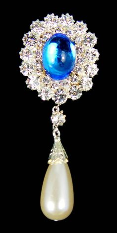 The Empress Marie Brooch consists of a large cabochon sapphire which is surrounded by 2 rows of diamonds. A large pearl drop hangs from the base. The brooch was purchased by Queen Mary from the Empress Marie's estate in 1929.