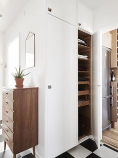 Dream hallway/entry room; the chess tiles, the mid-century dresser and the built-in wardrobe. Love it!