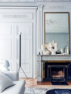 Two ceramic sculptures found at an Athens flea market are juxtaposed on the sitting room mantelpiece with a bird sculpture by Ghyslain Bertholon. The Flos 'Luminator' floor lamp is one of Achille and Pier Giacomo Castiglioni's classic designs.