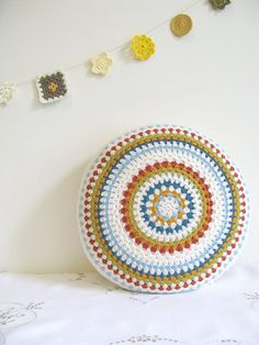 Cute round pillow/cushion.  Look at the crochet motif banner behind it too!