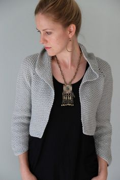 """While designing this shrug, I was inspired by the softness of a single-ply yarn worked in textured Seed Stitch and wanted to echo that feeling in gently curving lines in the garment itself. Short rows were the perfect way to achieve this, so I incorporated them into all horizontal edges of this shrug: the high collar, the bottom hem, and the sleeve cuff. The short rows and sloping edges also give the shrug body, and a bit of soft """"puff"""". The final piece is a pretty winter garment, chic…"""
