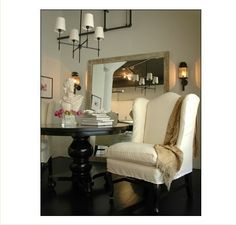 Small Space Solution: Oversize Floor Mirror next to round black table with wing chairs for DR/LR combo